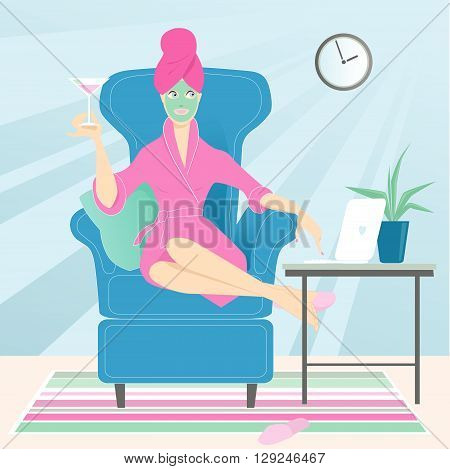 Cute woman sitting in a comfortable chair at home and working on her laptop in a bathrobe, with a towel on her head, facial mask on her face and a drink in her hand.