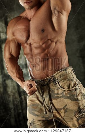 Torso of male bodybuilder posing flexing muscles.