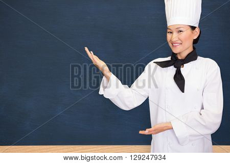 Portrait of a smiling female cook in kitchen against image of ac chalkboard