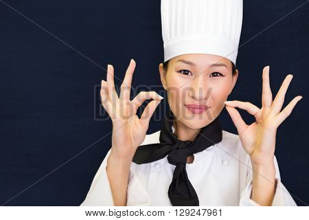 Closeup of a smiling female cook gesturing okay sign against navy blue