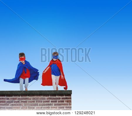 Masked kids running pretending to be superheroes against red brick wall