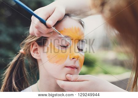 Child animator, artist's hand draws face painting to little girl. Child with funny face painting. Painter makes tiger eyes at girl's face. Children holiday, event, birthday party, entertainment.