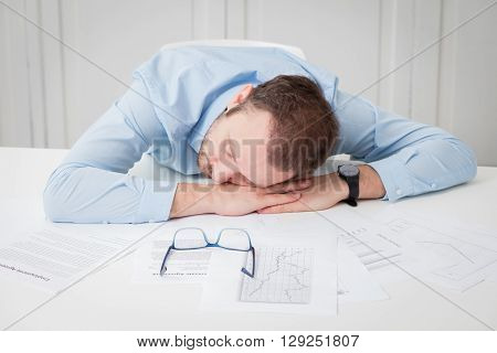 Tired businessman sleeping at the office desk