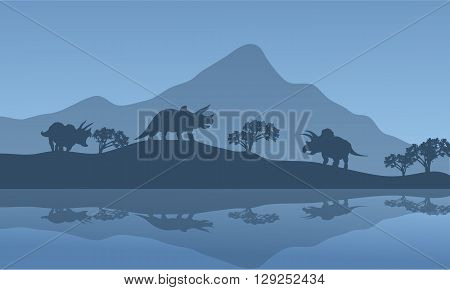 Silhouette of triceratops in the riverbank with blue backgrounds