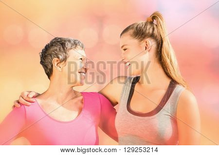 Colorful background against sporty mother and daughter smiling at each other