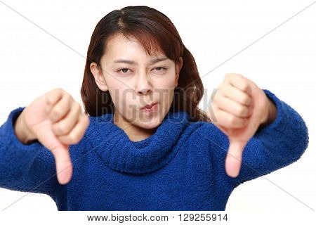 Asian woman with thumbs down gesture on white background