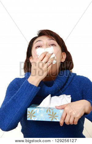 woman with an allergy sneezing into tissue