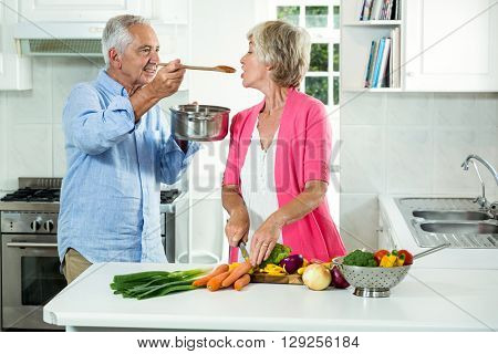 Smiling senior man feeding food to woman while standing in kitchen