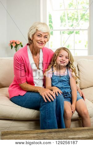Portrait of smiling granny and girl sitting on sofa at home