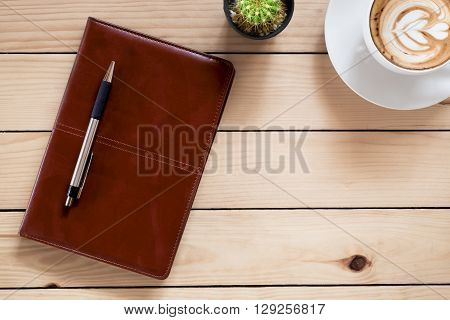 Office stuff with leather notebook coffee cup and cactus.Top view with copy space