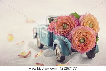 Old antique toy truck carrying a roses on romantic lace background