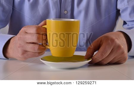 Businessman hands close up holding a yellow coffee cup
