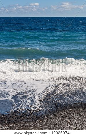 Stony coast and ocean waves with different tone colours vertical composition