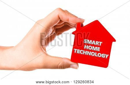 Smart home technology concept. Female hand with small model of house isolated on white