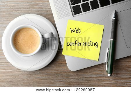 Web conferencing written on sticky note, laptop and cup of coffee on table, top view