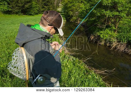 Fly fisherman chooses a fly for flyfishing trout