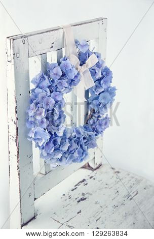 Blue hydrangea flower wreath on vintage wooden bakcground