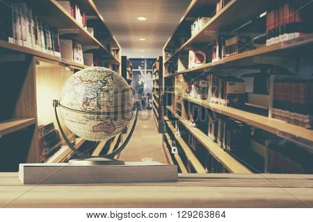 Globe model on textbook book on old age wood table with blur abstract campus library background