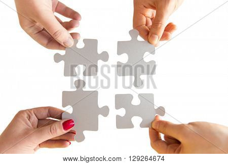 business, teamwork, cooperation, compatibility and connection concept - close up of hands connecting puzzle pieces