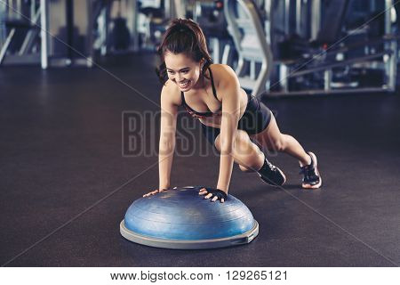 Cheerful Asian woman training with bosu ball