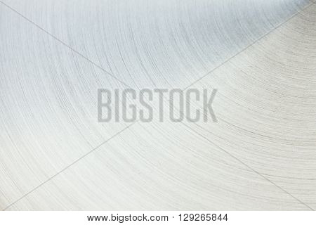 The polished silver surface. The semicircular line. The background.