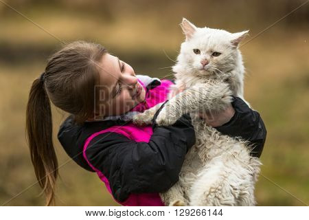 Ten-year girl playing with a stray cat.