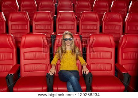 cinema, technology, entertainment and people concept - young woman with 3d glasses watching movie alone in empty theater auditorium