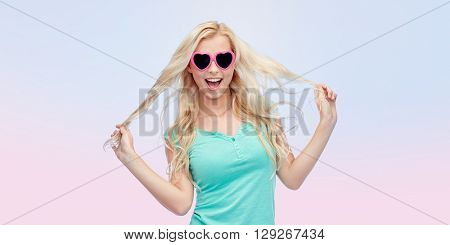 emotions, expressions, summer and people concept - smiling young woman or teenage girl in sunglasses holding her strand of hair over rose quartz and serenity gradient background