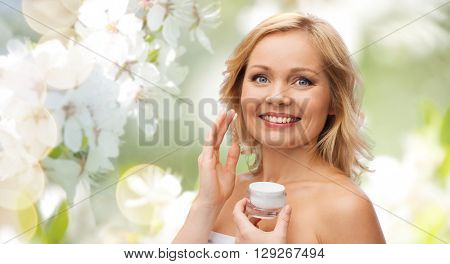 beauty, people, skincare and cosmetics concept - happy woman applying cream to her face over natural spring cherry blossom background