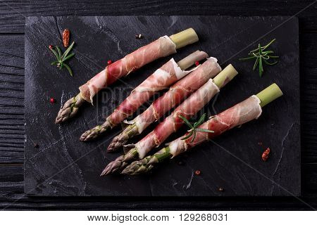 Fresh Organic Asparagus Wrapped In Parma Ham On A Cutting Board