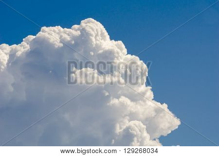 Big white cloud against bright blue sky
