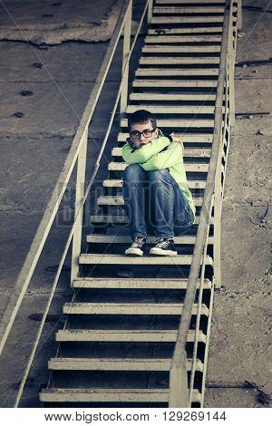 Sad teen boy in depression sitting on the steps