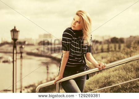 Happy young fashion blond woman. Female fashion model outdoor