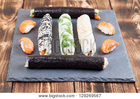 Homemade sushi rolls on a slate board