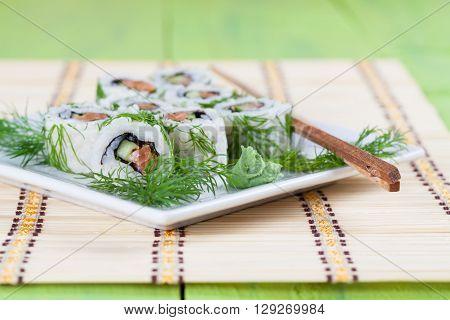 Uramaki sushi with cucumber raw salmon and dill. Shallow dof