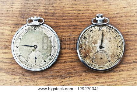 Old pocket watch on a wooden background