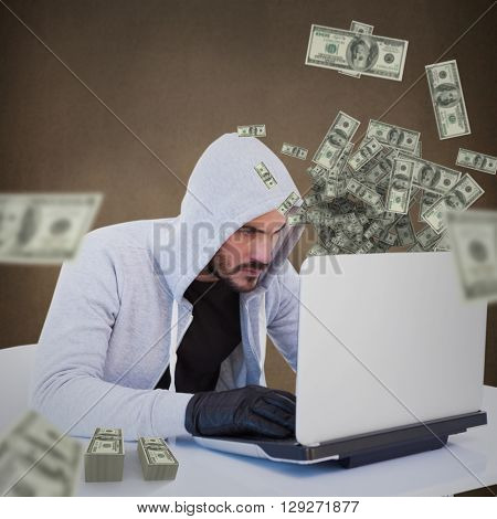 Serious burglar hacking into laptop against maroon background