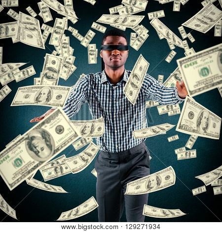 Blindfolded businessman with arms out against blue background