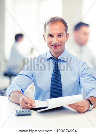 middle-aged businessman with notebook and calculator in office