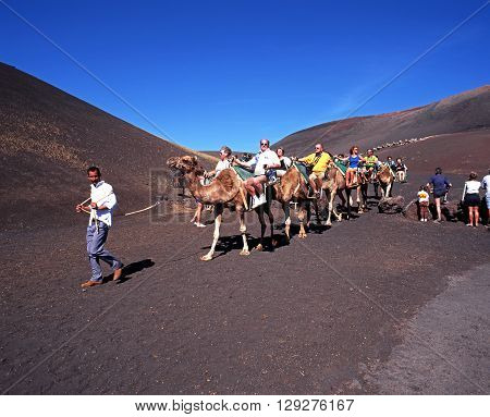 LANZAROTE, SPAIN - MARCH 3, 1998 - Tourists taking a camel ride through Timanfaya National Park Lanzarote Canary Islands Spain, March 3, 1998.