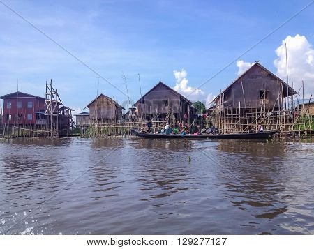 INLE LAKE MYANMAR - MAY 26 2014 : Local people are on longtail boat in front of Floating village at Inle Lake Myanmar