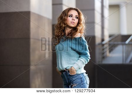 Happy young fashion woman walking on city street. Female fashion model with long curly hairs outdoor
