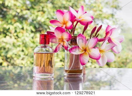 Bottle Of Sweet Pink Fragrant Perfume With Pink Flower Plumeria And Tree Background