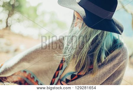 Beautiful young woman wearing in poncho and hat walking in summer forest