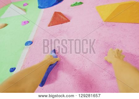 Female climber hands holding artificial boulder in climbing gym point of view shot