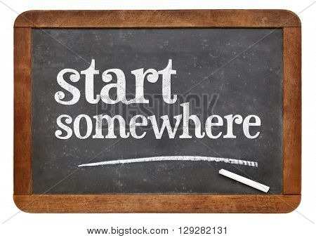 Start somewhere  - white chalk text on a vintage slate blackboard