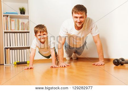 Young father and his kid son working out together, pushing up at the room