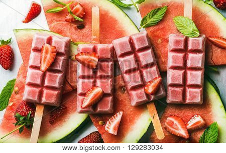 Strawberry watermelon ice cream popsicles with mint over steel tray background. Top view, horizontal