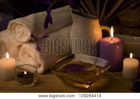Close-up. Spa still life. Sea salt bath massage oil candles flowers and towels. Body Oil. Iris flowers.