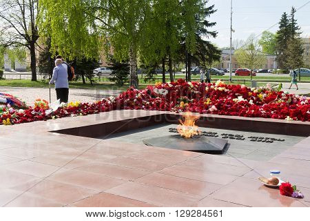 PETROZAVODSK, RUSSIA - MAY 10TH, 2016: Eternal fire against flowers after May 9th day of great victory, celebration of the victory in the second world war